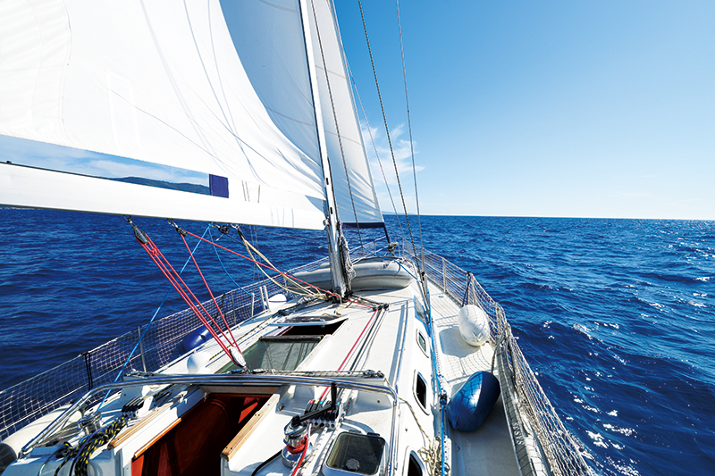 [photo] Point-of-view from the front of a white sailboat looking out into the blue ocean and clear sky