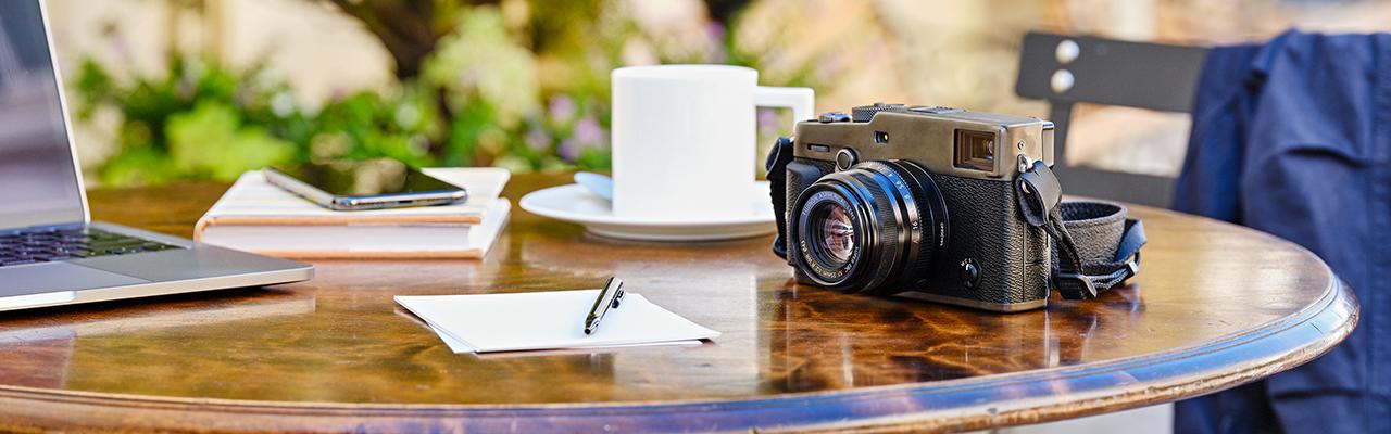 [fotografía] Una cámara digital Fujifilm sobre una mesa de jardín con otros materiales de escritura en el exterior