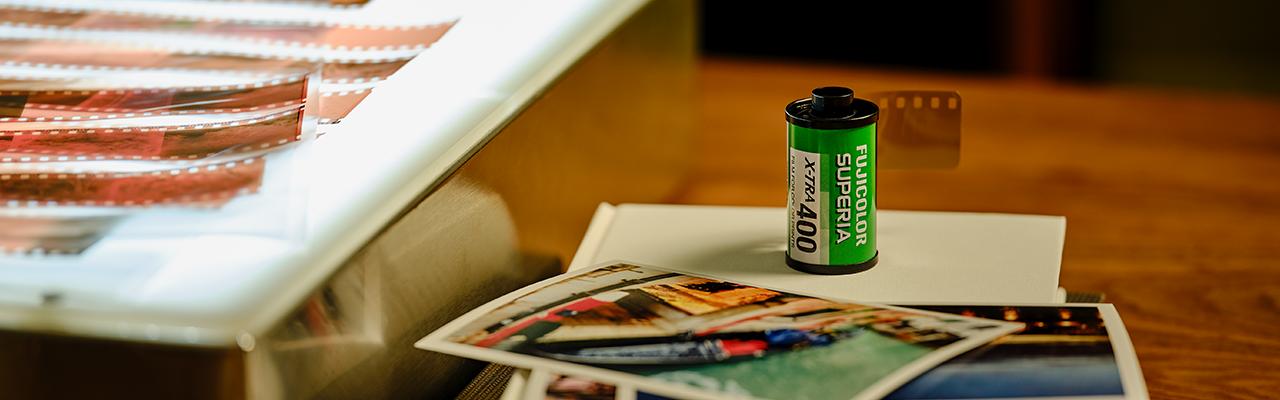 [fotografía] Película Fujicolor Superia X-Tra 400 sobre un libro de mesa blanco, y una impresión de muestra y negativos de película al lado