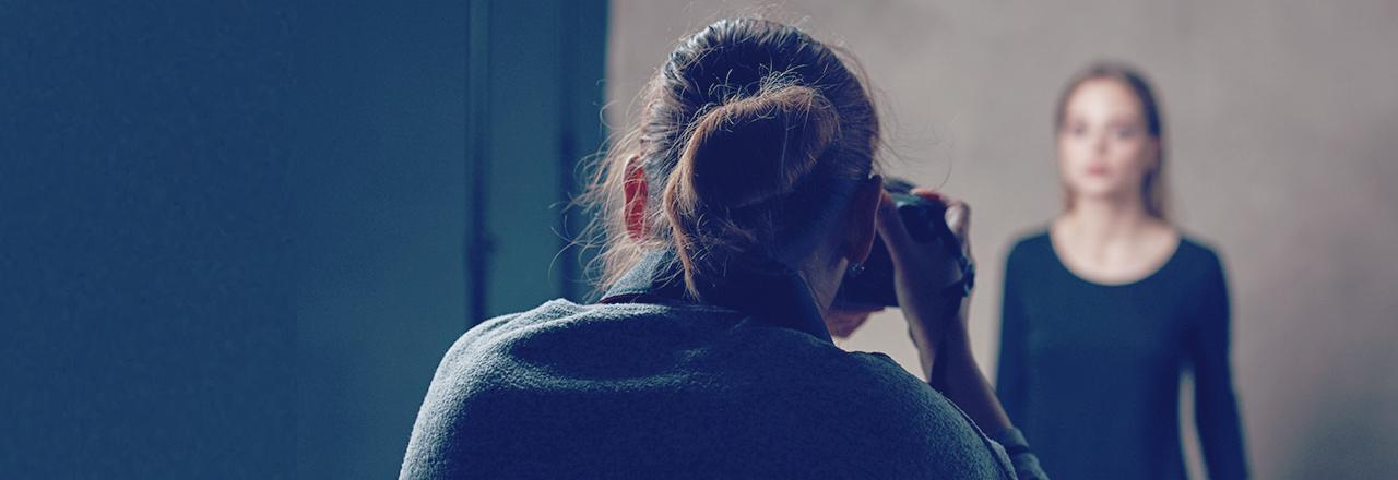 [foto] Una mujer mira a través de la cámara y toma fotos de otra mujer con un fondo borroso