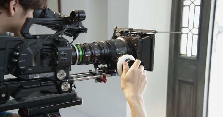 [photo] A cameraman's hand on a follow-focus wheel attached to an XK Lens on a Sony Camera