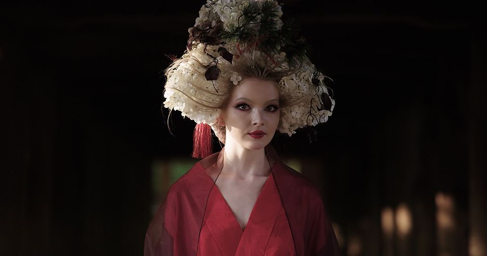 [photo] A medium view of a lady in traditional Japanese head gear and attire standing in a some dark room