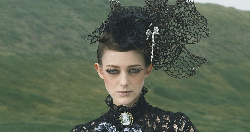 [photo] A face close-up of a lady dressed in a mediaval dress & hat sitting on a green grass on a cloudy day