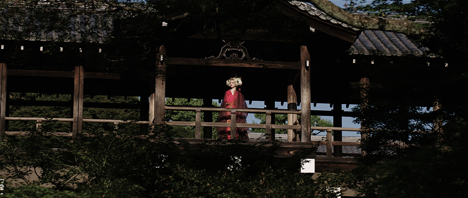 [photo] A very wide shot of a lady in traditional Japanese attire standing under a tradional Japanese wooden house
