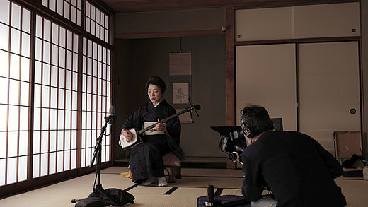 [photo] Man filming another man in a robe, playing a shamisen instrument