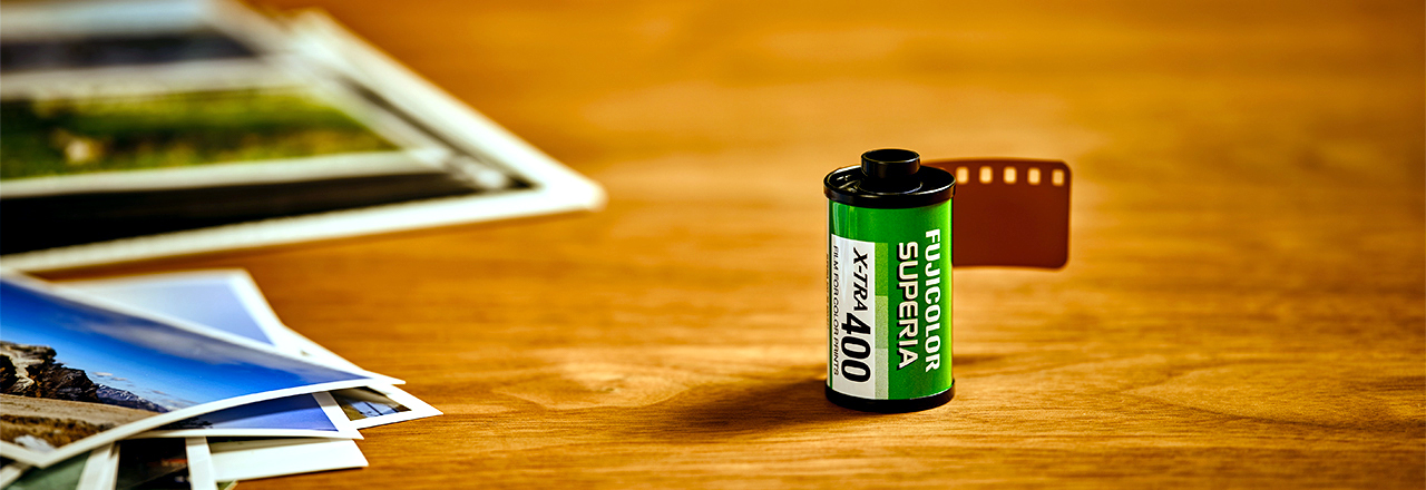 [photo] Fujicolor Superia X-Tra 400 film on a wooden table with some sample photos