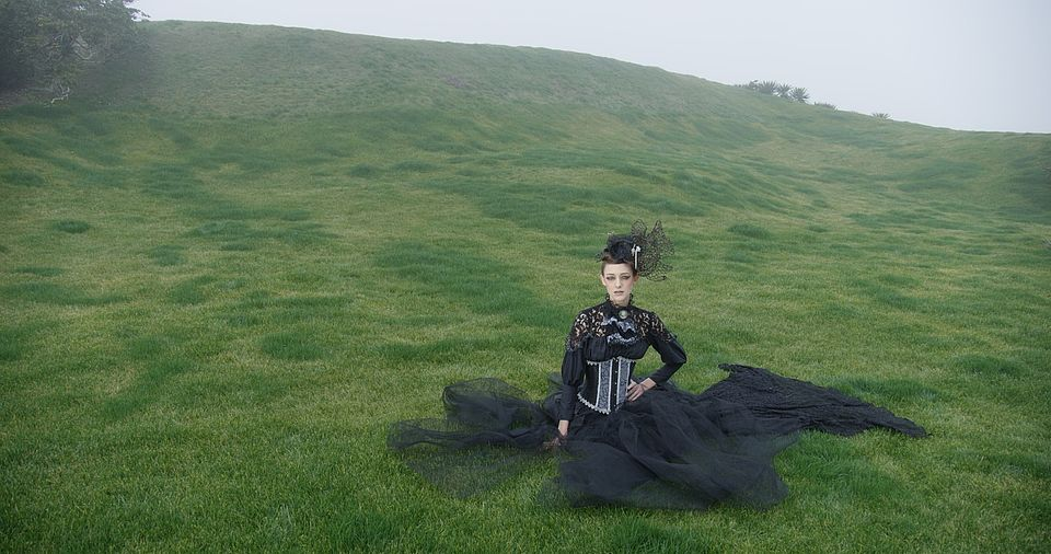 [photo] A wide shot of a lady dressed in a mediaval outfit sitting on a green grass on a cloudy day