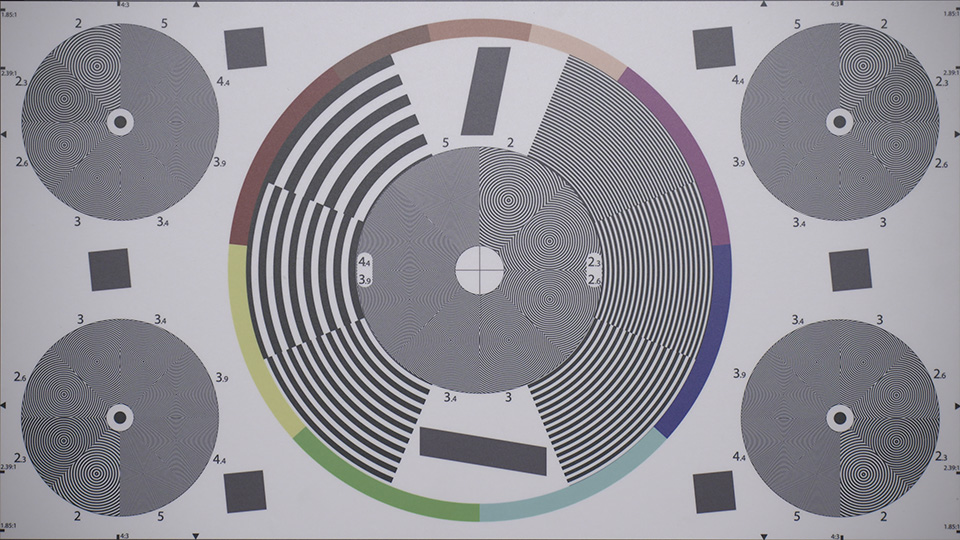 [photo] One big circle and 4 smaller circles with wavy lines on a lens test chart