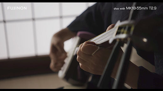 [photo] Close-up of hands playing a shamisen instrument