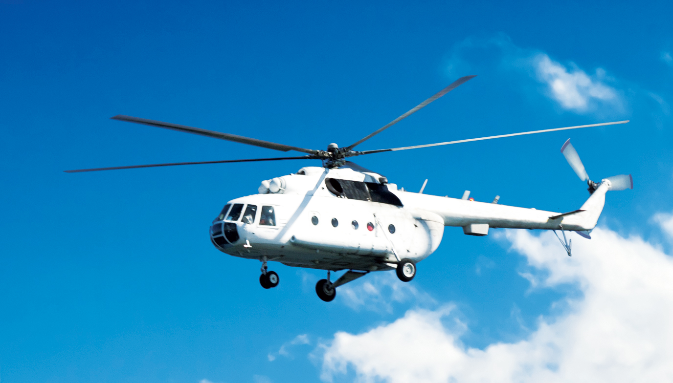 [photo] White helicopter flying in blue sky with sparse clouds