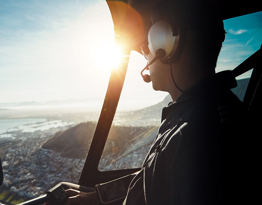 [photo] Pilot looking out the window of helicopter cockpit and sun shining bright in distance over horizon