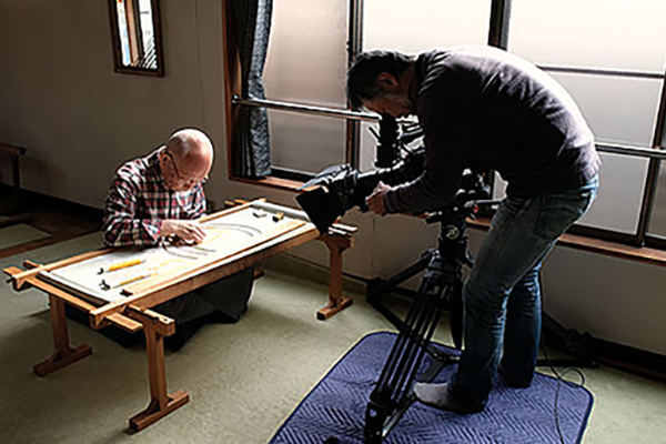 [photo] A cameraman shooting an older gentleman working with rulers on a table