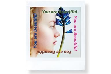 "[photo] A girl staring at a blue flower and the words ""You are beautiful"" written along the 4 sides of the photo."