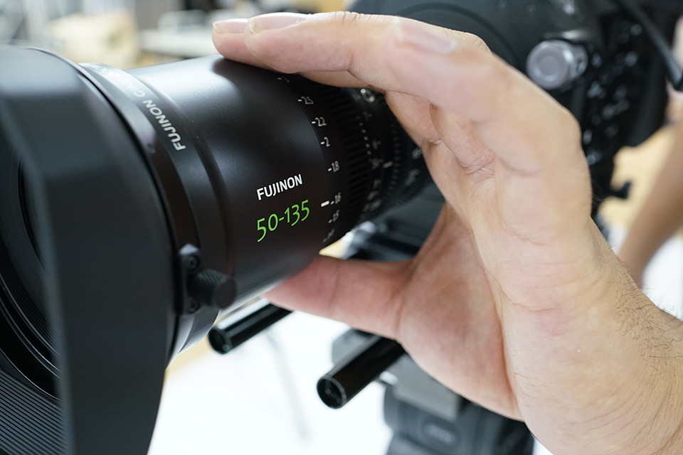 [photo] Close up view of a camera operator's hand on the focus ring of an MK Series lens