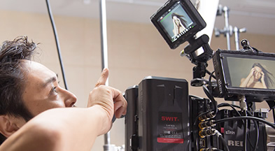 [photo] A cameraman pointing to the external monitor display of a digital camera he's looking at