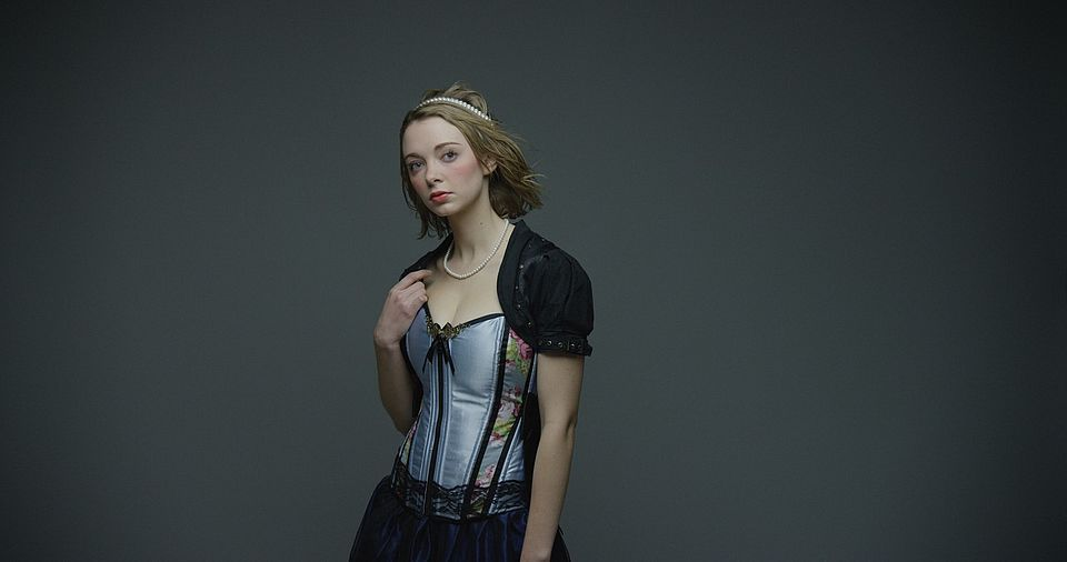 [photo] A medium shot of a lady dressed in a mediaval outfit standing infront of a gray wall