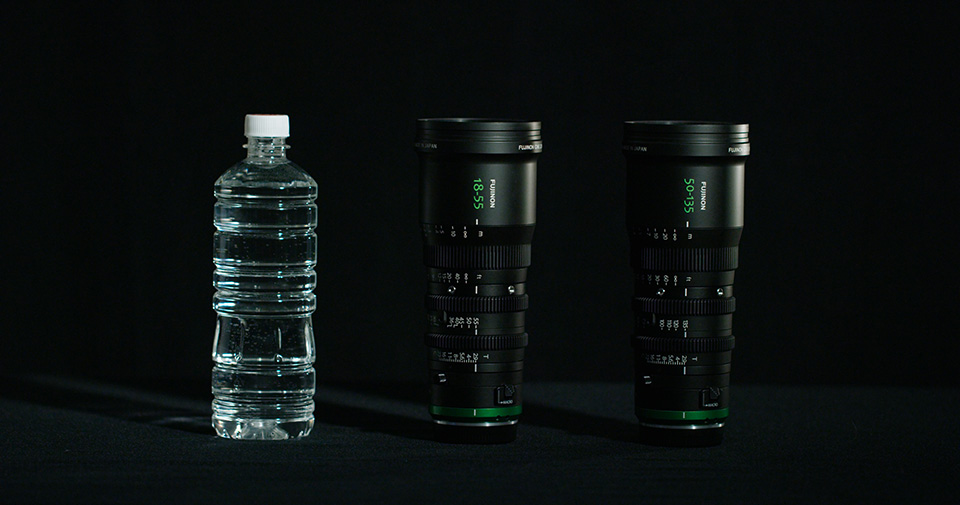 [photo] A bottle of water next to the MK Series lenses on a black background