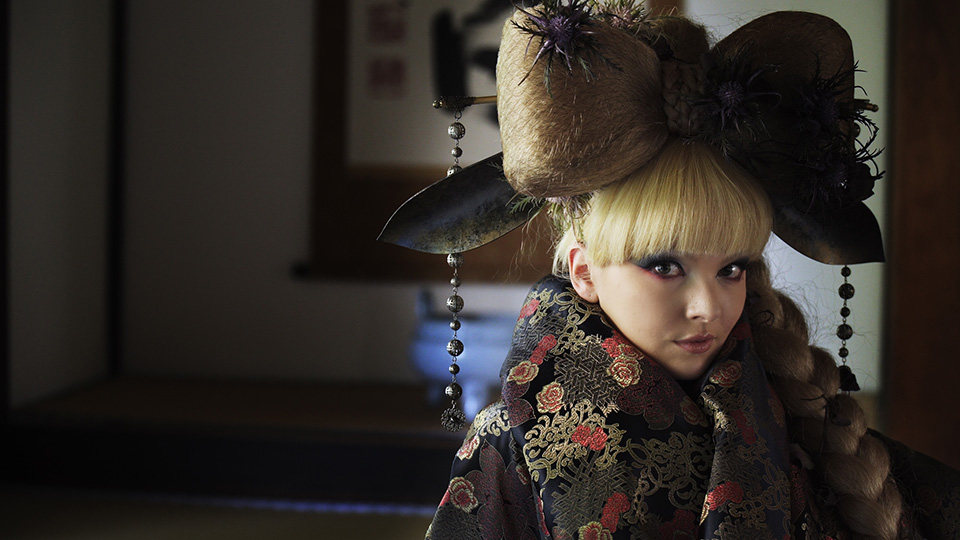 [photo] Close up of an actress in traditional Japanese headgear and attire standing infront of Japanese art indoors