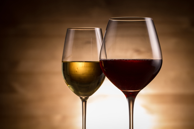 [photo] Two glasses of wine, one red and one white, in front of dimmed, amber background