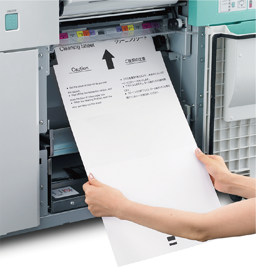 [photo] Woman feeding a cleaning sheet of paper into the paper feed of printer