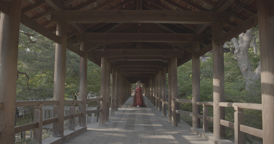 [photo] A less saturated version of a lady in traditional Japenese attire standing under a wooden bridge