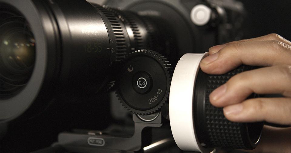 [photo] A cameraman's had on a follow-focus wheel attached to an MK Series lens