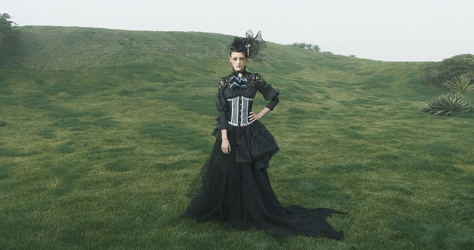 [photo] A wide shot of a lady dressed in a mediaval dress & hat standing on a green grass field on a cloudy day