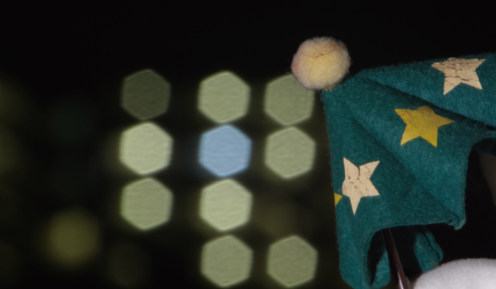 [photo] Green, cloth umbrella in foreground with blurred hexagonal lights in background