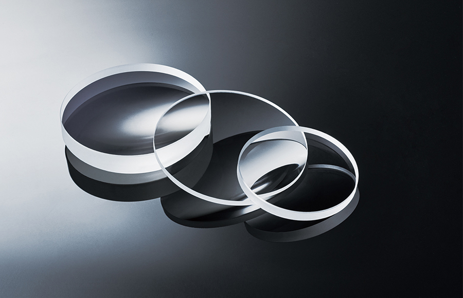 [photo] Three flat, glass discs fanned out on top of each other in a straight line on a dark, flat surface