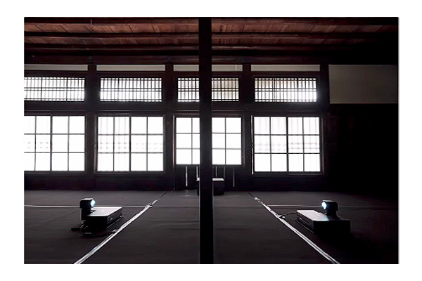 [photo] A big empty room with large windows and two projects at the center facing each other