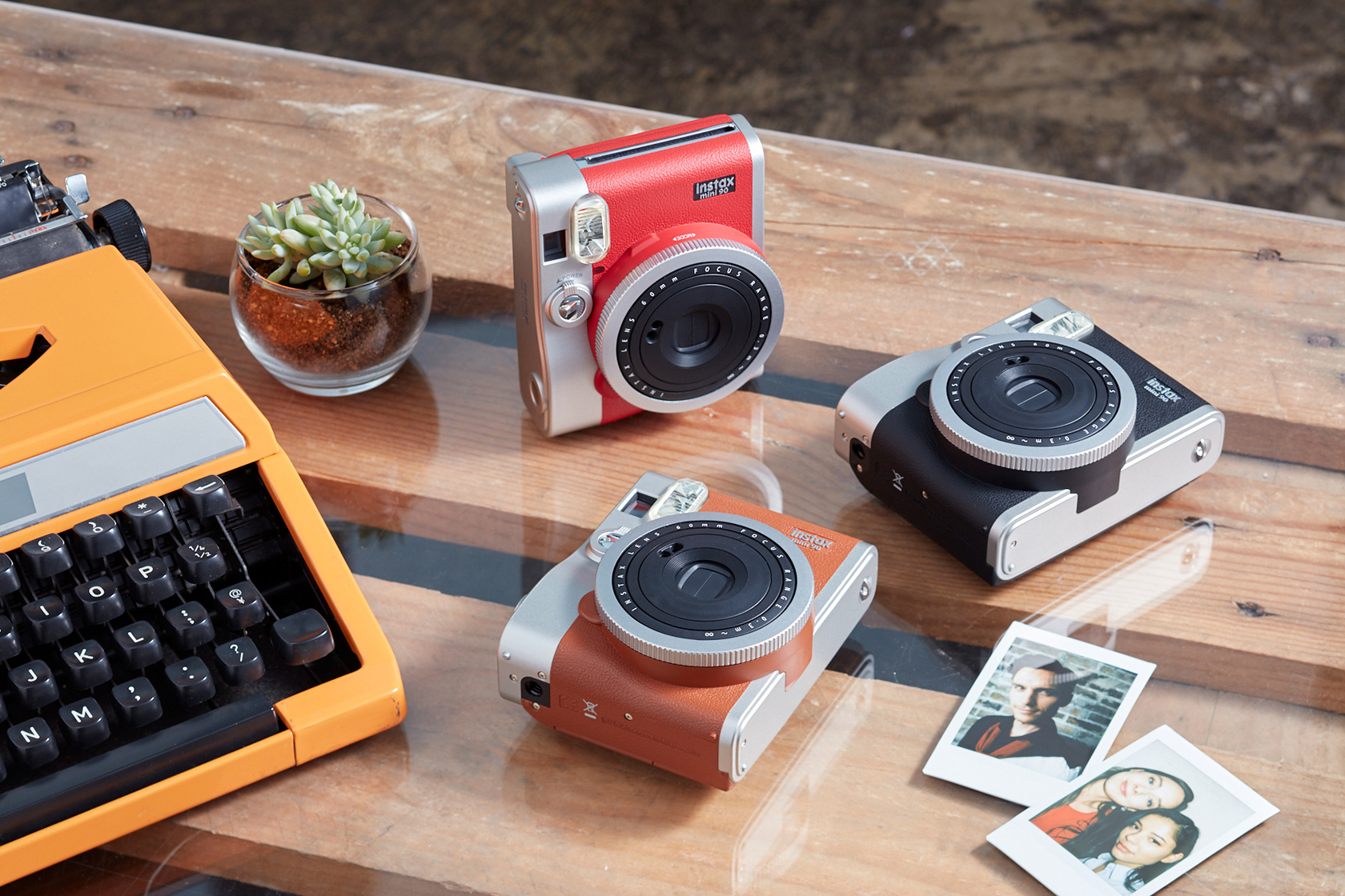 Three mini 90 camera in different color with two photos and typewriter on table