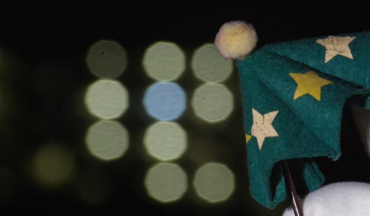 [photo] Green, cloth umbrella in foreground with blurred spherical lights in background