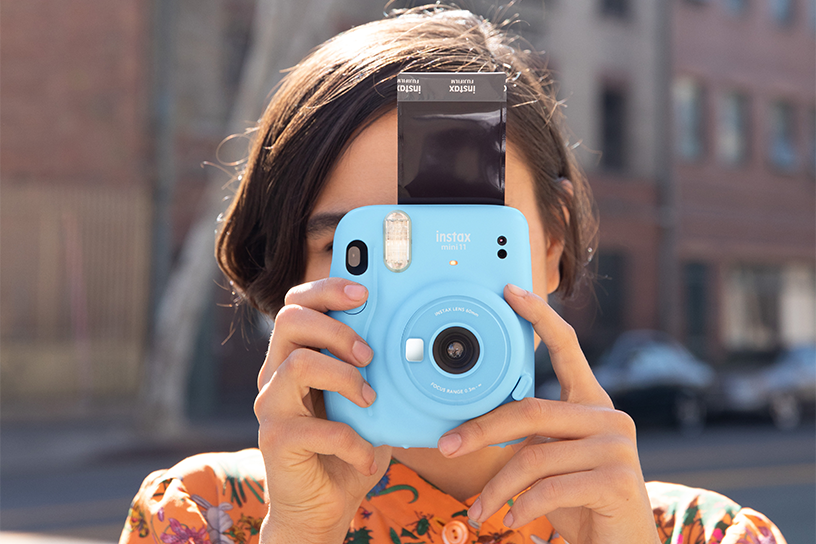 Image of woman taking photo with baby blue Mini 11 camera