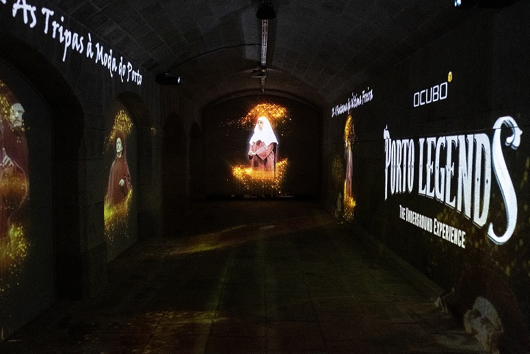 [photo] Woman in red robe and white hood being projected at far end of dark room, with images of actors and words projected unto side walls