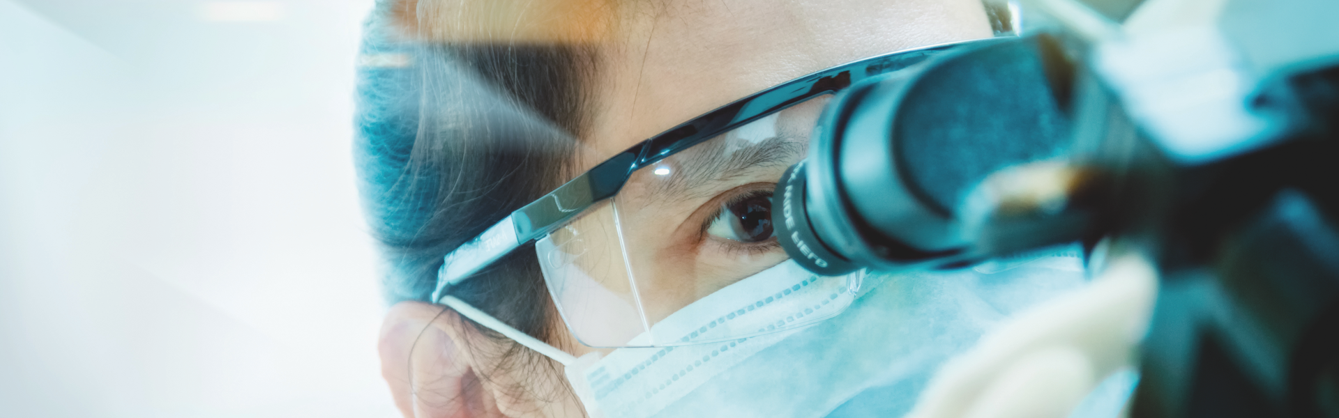 Man wearing surgical mask and safety goggles looking into a microscope