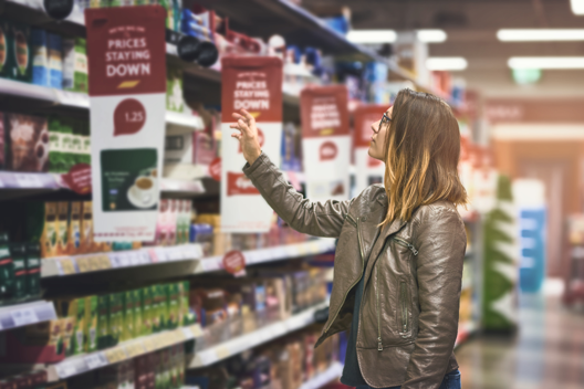 Women in store aisle with banner media attached to shelves
