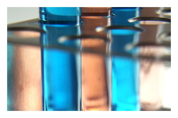 Two vials of blue liquid in vial rack