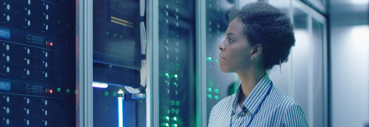 [photo] Woman in blue-striped dress shirt looking at data storage machines
