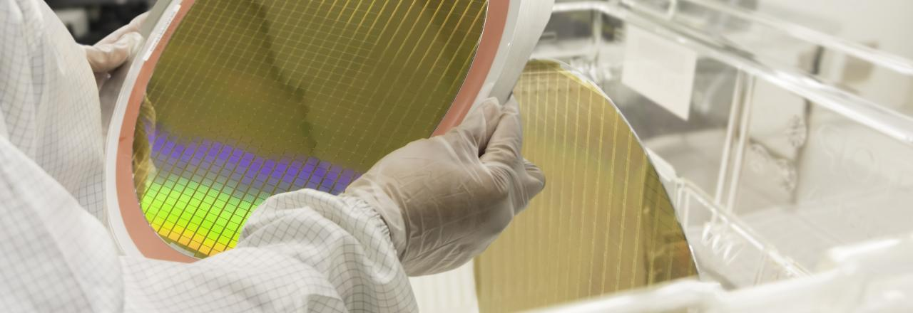 Hands of Engineer in white gloves holding a Silicon wafers