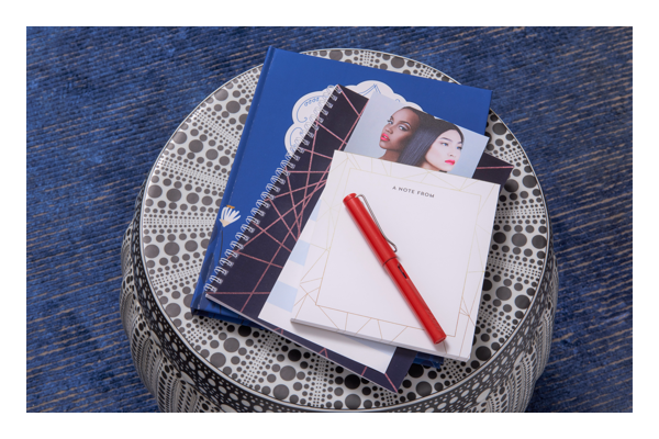 image of notebooks and red pen on a round table