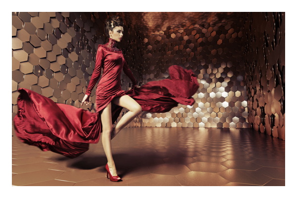 Women in red dress stepping through room with hexagon textured walls