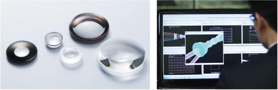[photo] Various glass lens parts and man looking at computer with lens blueprints on screen